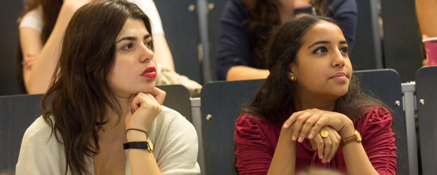 Two young women in a lecture hall