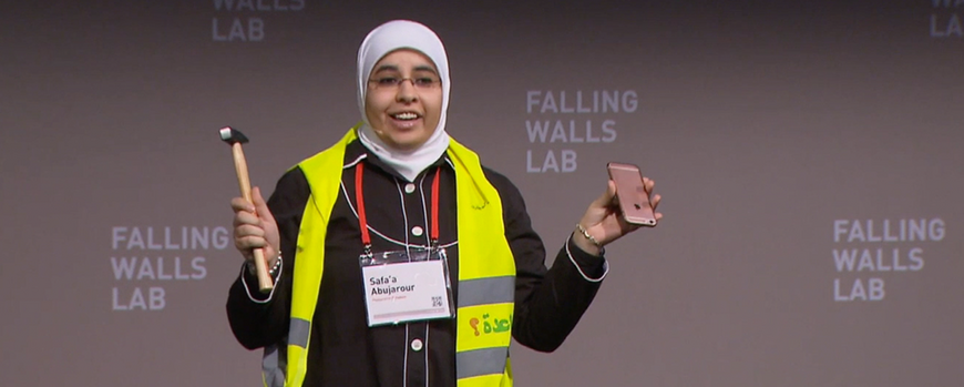 Safa'a holding up hammer and smartphone on the stage