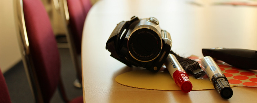 Camcorder, penscils and other materials arranged on a table