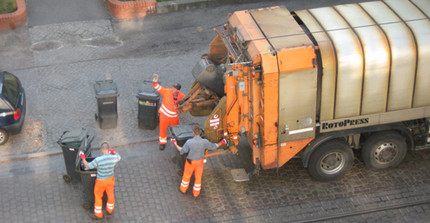 three man in orange clothes behind a garbidge collection truck